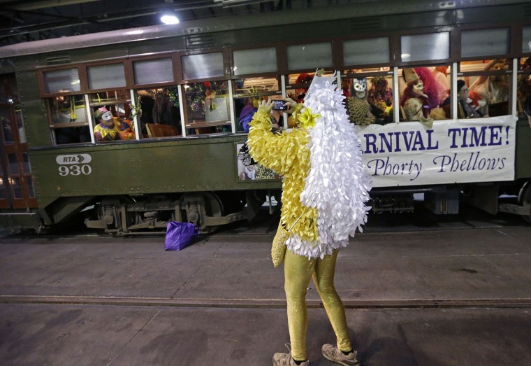 A members of the Phunny Phorty Phellows takes photos as they disembark a streetcar during their night of revelry in New Orleans, Tuesday, Jan. 6, 2015. King's Day is a tradition marking the 12th night after Christmas and the official start of the Mardi season. Carnival is celebrated along the Gulf Coast with parties, balls and parades culminating on Mardi Gras, or Fat Tuesday, a final day of celebration before Lent. It is a major tourist draw in New Orleans. Mardi Gras falls on Feb. 17 this year. (AP Photo/Gerald Herbert)