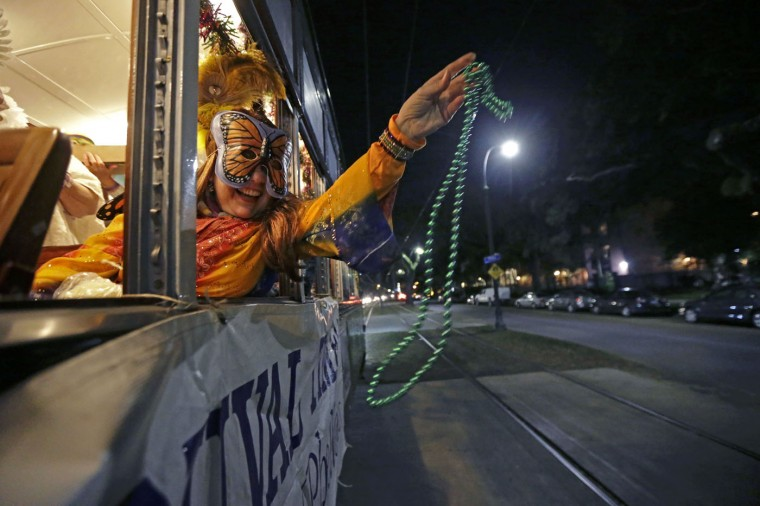 Members of the Phunny Phorty Phellows, toss beads during their night of revelry aboard a streetcar in New Orleans, Tuesday, Jan. 6, 2015. King's Day is a tradition marking the 12th night after Christmas and the official start of the Mardi season. Carnival is celebrated along the Gulf Coast with parties, balls and parades culminating on Mardi Gras, or Fat Tuesday, a final day of celebration before Lent. It is a major tourist draw in New Orleans. Mardi Gras falls on Feb. 17 this year. (AP Photo/Gerald Herbert)