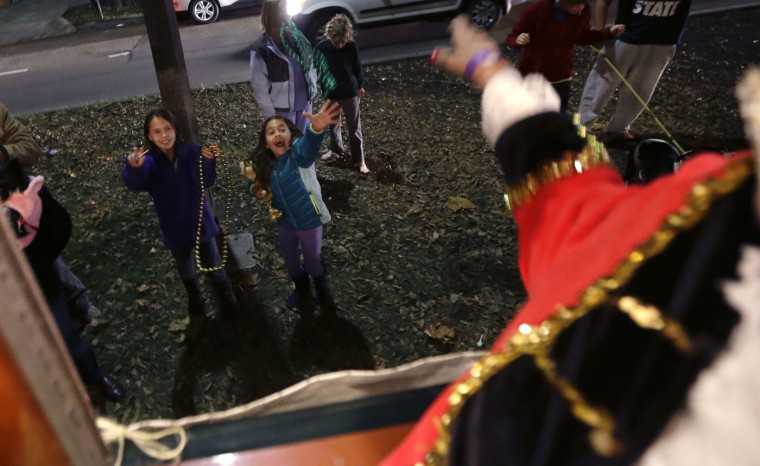 Members of the Phunny Phorty Phellows, toss beads to children during their night of revelry aboard a streetcar in New Orleans, Tuesday, Jan. 6, 2015. King's Day is a tradition marking the 12th night after Christmas and the official start of the Mardi season. Carnival is celebrated along the Gulf Coast with parties, balls and parades culminating on Mardi Gras, or Fat Tuesday, a final day of celebration before Lent. It is a major tourist draw in New Orleans. Mardi Gras falls on Feb. 17 this year. (AP Photo/Gerald Herbert)
