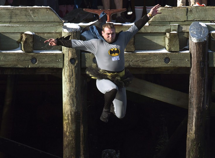 A man wearing a Batman suit and a tutu leaps from the government wharf into the frigid North Atlantic in the annual New Year's Day polar bear swim in Herring Cove, N.S. on Thursday, Jan. 1, 2015. (Andrew Vaughan/AP Photo/The Canadian Press)