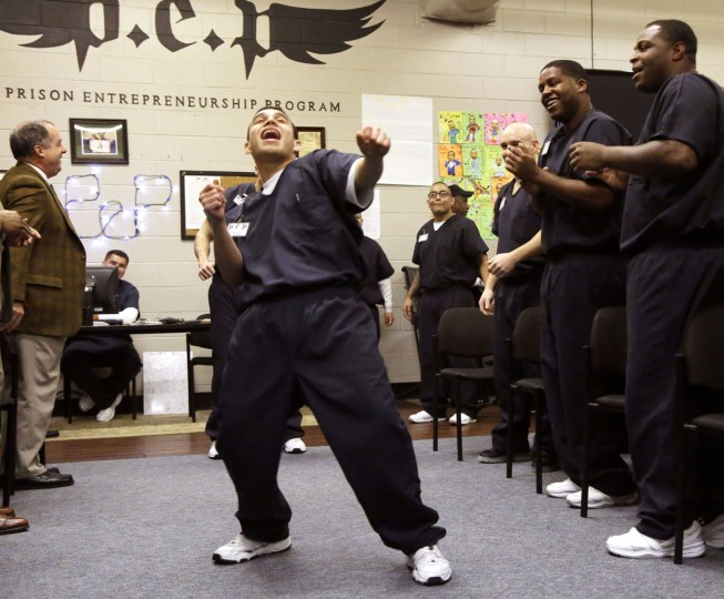 In this photo taken Dec. 12, 2014, prison inmate Nicholas Paz, center, dances down a a line of his classmates in the Prison Entrepreneurship Program, or PEP, right, and program sponsors, in Cleveland, Texas. (AP Photo/Pat Sullivan)