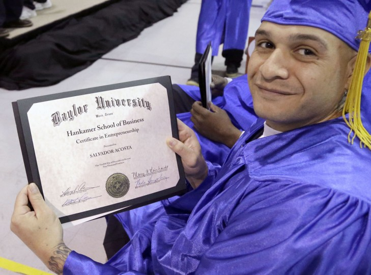 In this photo taken Dec. 12, 2014, prison inmate and graduate of the Prison Entrepreneurship Program Salvador Acosta proudly displays his Baylor Universityís Hankamer School of Business certificate of entrepreneurship during graduation ceremonies at the Cleveland Correctional Facility in Cleveland, Texas. (AP Photo/Pat Sullivan)
