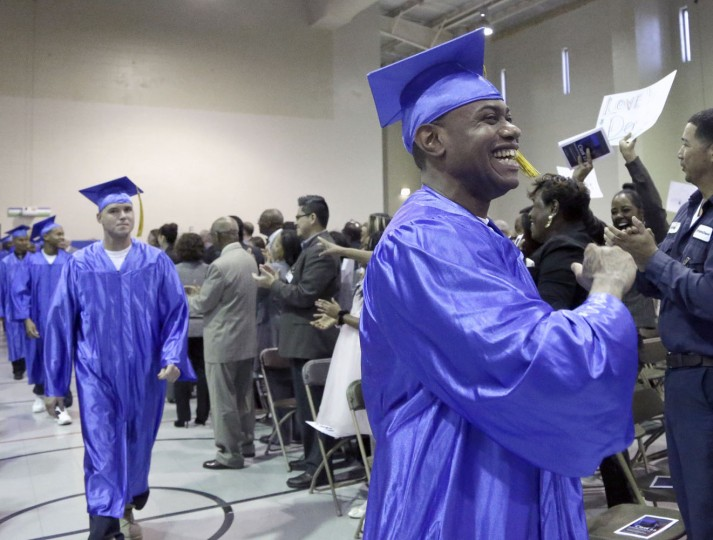 In this photo taken Dec. 12, 2014 shows inmates, in caps and gowns in the Prison Entrepreneurship Program marching toward the stage for graduation ceremonies, at the Cleveland Correctional Facility in Cleveland, Texas. (AP Photo/Pat Sullivan)
