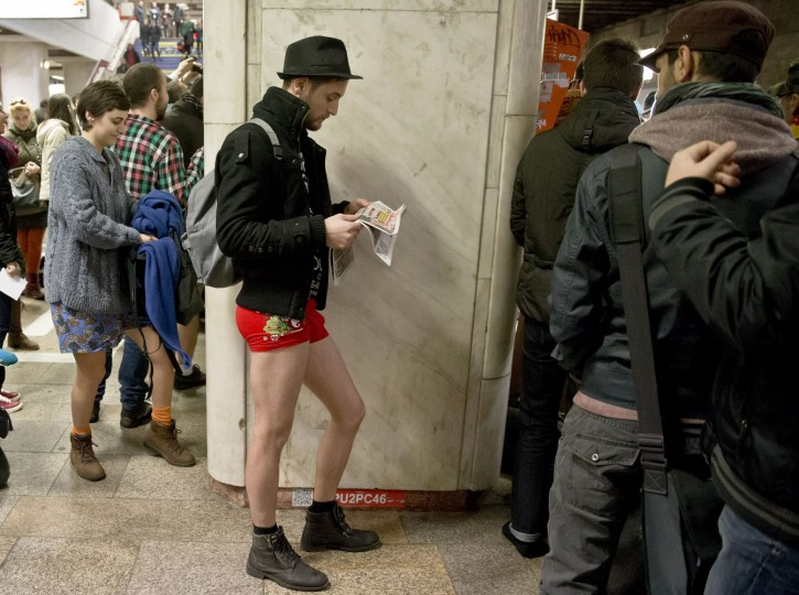 A man reads a newspaper as he takes part in the first edition of the No Pants Subway Ride in Bucharest, Romania, Sunday, Jan. 11, 2015. The No Pants Subway Ride began in 2002 in New York as a stunt and has taken place in cities around the world since then. Organizers call it ìan international celebration of sillinessî and are organizing it in dozens of cities on Sunday. (AP Photo/Vadim Ghirda)