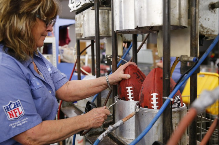 Doris Kast places an official game ball for NFL football's Super Bowl XLIX in a molding press for the final shaping at the Wilson Sporting Goods Co. in Ada, Ohio, Tuesday, Jan. 20, 2015. The New England Patriots face the Seattle Seahawks for the NFL championship on Sunday, Feb. 1, 2015, in Glendale, Ariz. (AP Photo/Rick Osentoski)