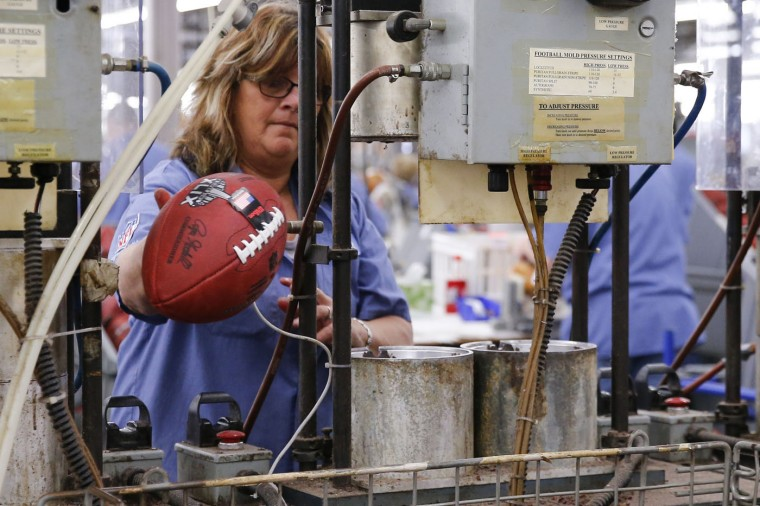 Doris Kast tosses an official game ball for NFL football's Super Bowl XLIX into a bin after it is removed from a molding press at the Wilson Sporting Goods Co. in Ada, Ohio, Tuesday, Jan. 20, 2015. The New England Patriots face the Seattle Seahawks for the NFL championship on Sunday, Feb. 1, 2015, in Glendale, Ariz. (AP Photo/Rick Osentoski)