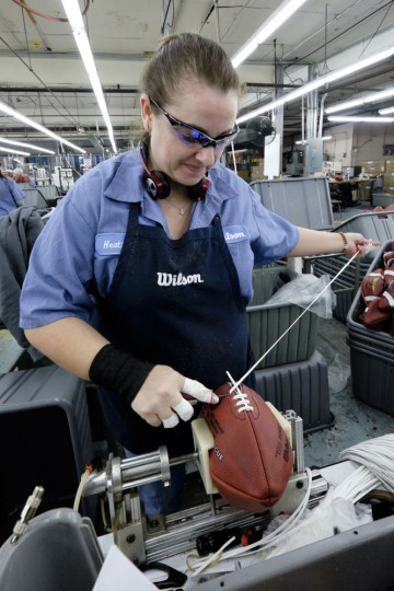 Heather Wireman laces up an official game ball for the NFL football Super Bowl XLIX at the Wilson Sporting Goods Co. in Ada, Ohio, Tuesday, Jan. 20, 2015. The New England Patriots will play the Seattle Seahawks in the Super Bowl on Feb. 1 in Glendale, Arizona. (AP Photo/Rick Osentoski)