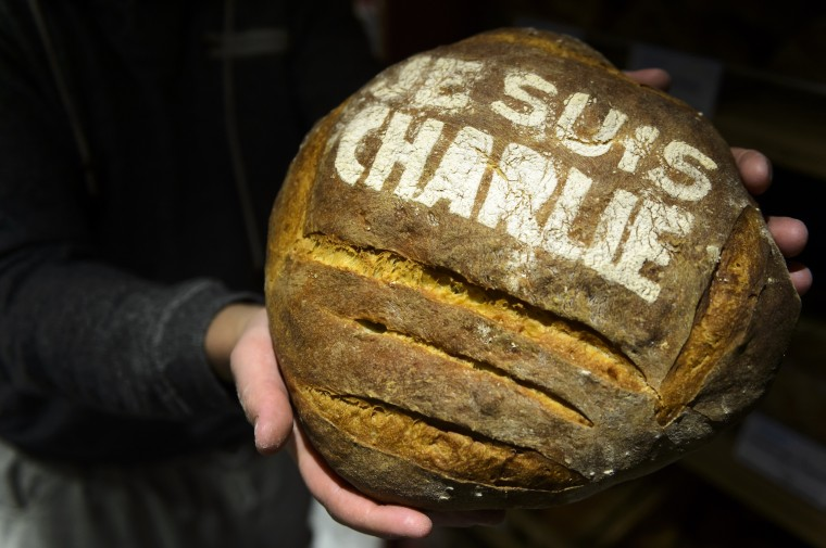"Baker Pascal Clement holds a loaf of bread with ""Je suis Charlie"" (I am Charlie) written on it in commemoration to the victims of Charlie Hebdo newspaper, Friday, Jan. 9, 2015, in Daillens, Switzerland. Masked gunmen stormed the Paris offices of the weekly newspaper that caricatured the Prophet Muhammad, methodically killing 12 people at the offices of the paper, Wednesday, including the editor, before escaping in a car. It was France's deadliest postwar terrorist attack. (AP Photo/Keystone, Laurent Gillieron)"