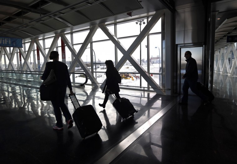 Travelers move through Logan International Airport in Boston Wednesday, Jan. 28, 2015, as it begins to resume normal operations one day after a blizzard dumped about two feet of snow in the city. (AP Photo/Elise Amendola)