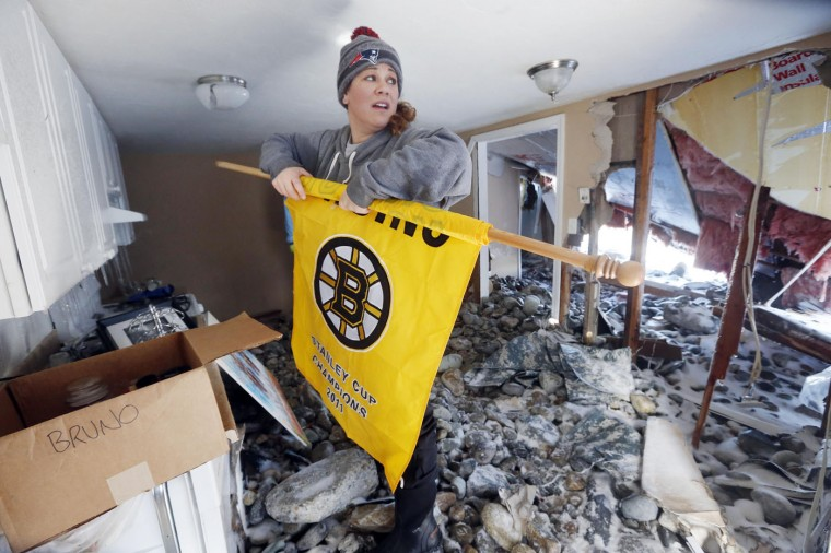 Jennifer Bruno gathers belongings inside her heavily damaged apartment the day after a winter storm in Marshfield, Mass., Wednesday, Jan. 28, 2015. The storm buried the Boston area in more than 2 feet of snow and lashed it with howling winds that exceeded 70 mph. (AP Photo/Michael Dwyer)