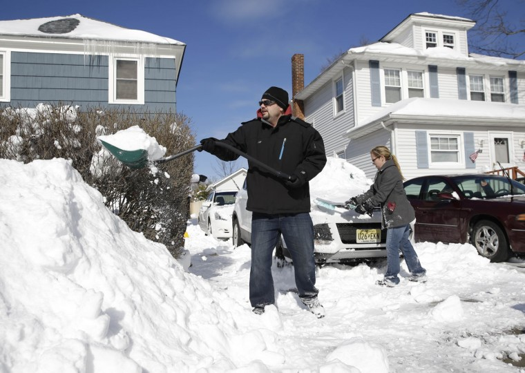 Shane, left, and Dawn Perry clear snow from their driveway and cars in Patchogue, N.Y., Wednesday, Jan. 28, 2015. While much of the New York City region breathed easier after eluding serious damage from a deadly blizzard, highway crews helped eastern Long Island residents recover from a storm that dumped more than two feet of snow in some places. (AP Photo/Seth Wenig)
