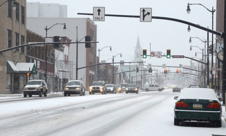 Motorists travel along Broad Street in Hazleton Pa., as light snow falls on the area Tuesday Jan. 6, 2015. Snow delayed the start of school and reduced speeds on highways in western Pennsylvania and slowed commuter rail and air travel in the Philadelphia area. (AP Photo/Hazleton Standard-Speaker, Eric Conover)