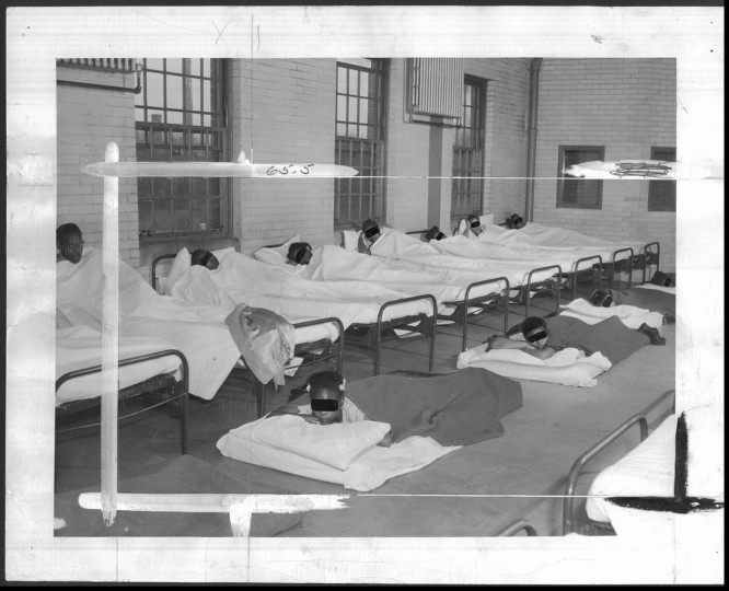Teenage girls sleep on mattresses between rows of beds in the children's building at Crownsville State Hospital. This is the only place in Maryland for feeble-minded black girls. Photo by Robert F. Kniesche, January 11, 1949