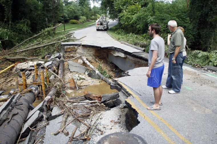 Residents look at the damage from a sinkhole on Marley Neck Rd. in Glen Burnie on Wednesday. (Baltimore Sun/Al Drago)