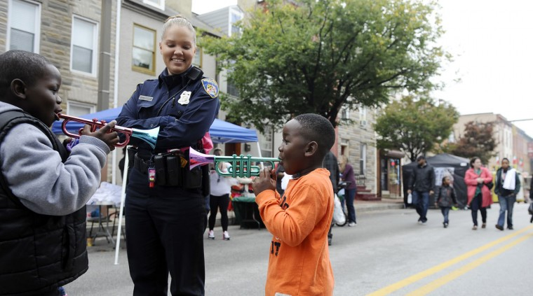 10/11/14: Detective Jessica Armstrong, office of the chief of CID, is serenaded by, left, Anthony Lewis, 7, and his brother, Dylan Rouse, 4, of Pigtown. They are at the 13th Annual Pigtown Festival. Kim Hairston/The Baltimore Sun