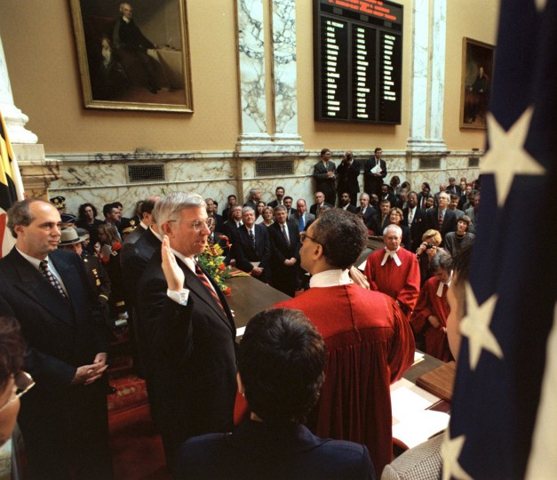 From left, Rabbi Stuart Weinblatt (who delivered the invocation) looks on as Gov. Parris Glendening center) is sworn in by Judge Robert Bell, who swore him in during the 1999 ceremony. In foreground with back to camera is wife Frances Glendening. (Baltimore Sun/Karl Merton Ferron)