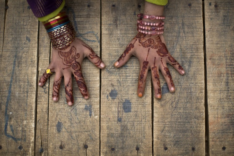 An Afghan refugee schoolgirl displays her hands decorated with Bangles and painted with Henna paste during class at a makeshift school on the outskirts of Islamabad, Pakistan, Monday, Jan. 12, 2015. Pakistani children and staff returned to a school in northwestern Pakistan where Taliban gunmen nearly a month ago killed 150 people ó almost all of them students. (AP Photo/Muhammed Muheisen)
