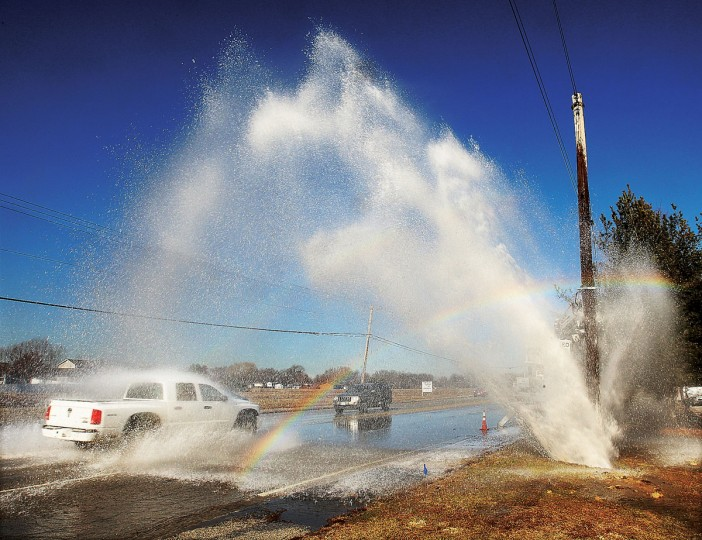 Cars drive by a faint rainbow as a water main rupture spews water across all four lanes of traffic on Humbert Road in Godfrey, Ill., Friday, Jan. 16, 2015. Numerous motorists took advantage of the water, deliberately stopping under it to wash the road salt off their vehicles. (AP Photo/The Telegraph, John Badman)