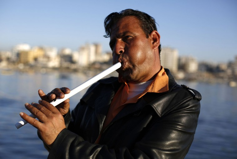 A Palestinian man plays the flute in Gaza City's sea front on January 21, 2015. (Mohammed Abed/AFP/Getty Images)