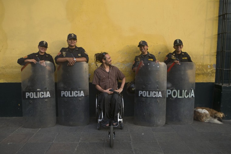 A tourist in a wheelchair poses for a picture with female police outside the government palace in downtown Lima, Peru, Thursday, Jan. 22, 2015. The police requested a group shot with him, using his camera, after he took pictures of them standing guard. (AP Photo/Esteban Felix)