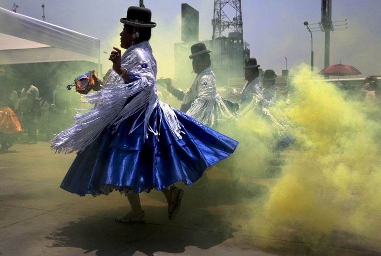 Dancers wearing bowler hats perform in a cloud of theatrical smoke in a pre-feast presentation in honor of Our Lady of Candelaria's upcoming feast day celebrations, in Lima, Peru, Thursday, Jan. 22, 2015. A 15-day festival takes place annually in the patron saint's honor in Puno, over 800 miles southeast of Lima. The cultural event, which begins Feb. 1, is recognized as one of the most popular and significant in South America. (AP Photo/Martin Mejia)