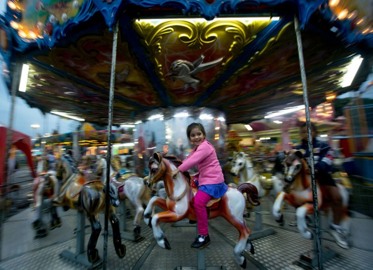 A girl rides on a carousel horse at the San Sebastian state fair in San Cristobal, Venezuela, Thursday, Jan. 22, 2015. (AP Photo/Fernando Llano)