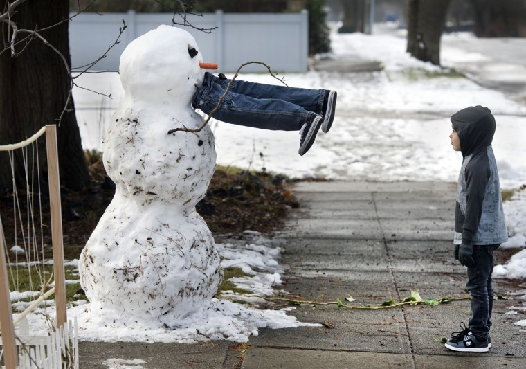 Miles McQuesten, 5, stands in front of a snowman, Friday, Jan. 23, 2015, in Spokane, Wash. The boy and his father, Rick, built the snowman Friday morning, and the legs are constructed from branches and newspapers. (AP Photo/The Spokesman-Review, Dan Pelle)