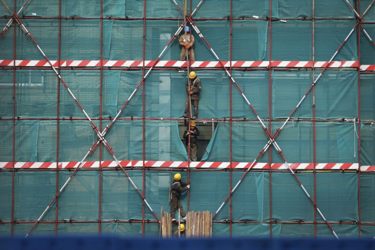 Construction workers stand on scaffolding to transfer iron bars at an office building which is being refurbished, in Beijing Saturday, Jan. 24, 2015. (AP Photo/Andy Wong)