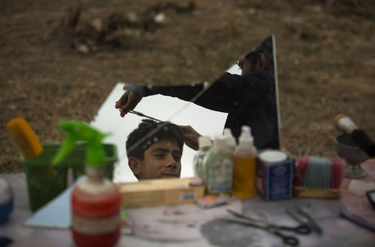 A Pakistani street barber gives a haircut to a customer, reflected on the mirror, on a roadside in Islamabad, Pakistan, Wednesday, Jan. 28, 2015. (AP Photo/B.K. Bangash)