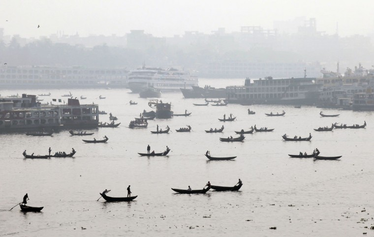 Bangladeshis on country boats cross the Buriganga River in Dhaka, Bangladesh, Thursday, Jan. 29, 2015. (AP Photo/ A.M. Ahad)