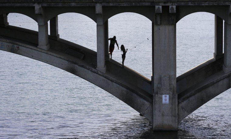 A couple plays under a bridge on Lady Bird Lake as they take advantage of spring-like weather, Thursday, Jan. 29, 2015, in Austin, Texas. (AP Photo/Eric Gay)