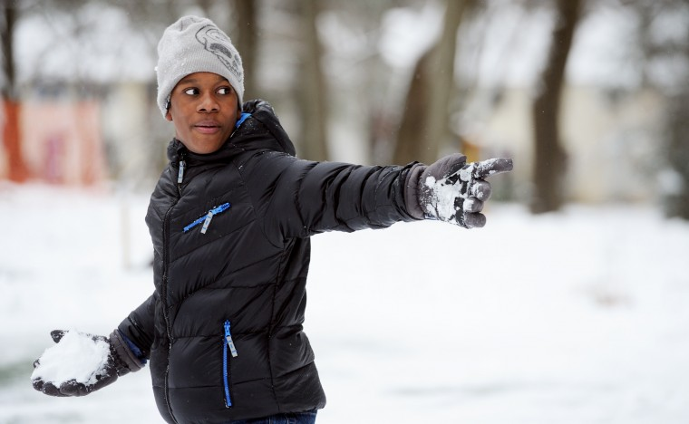 Jadon English, 11, of the Longfellow neighborhood in Columbia, takes aim with a snowball while playing with friends at a small park, Tuesday, Jan. 6, 2015. (Baltimore Sun Media Group)