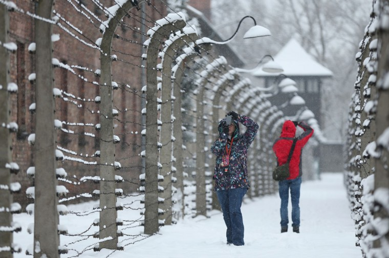 Visitors snap photos in between layers of barbed wire that surround the former Auschwitz I concentration camp, and which today is a museum, on January 25, 2015 in Oswiecim, Poland. International heads of state, dignitaries and over 300 Auschwitz survivors will commemorate the 70th anniversary of the liberation of Auschwitz by Soviet troops in 1945 on January 27. (Photo by Sean Gallup/Getty Images)