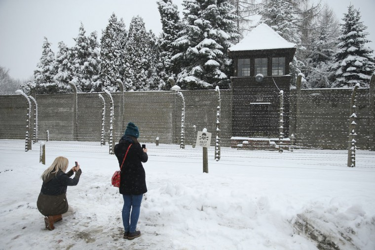 Visitors snap photos of barbed wire and a guard tower at the former Auschwitz I concentration camp, which today is a museum, on January 25, 2015 in Oswiecim, Poland. International heads of state, dignitaries and over 300 Auschwitz survivors will commemorate the 70th anniversary of the liberation of Auschwitz by Soviet troops in 1945 on January 27. Auschwitz was among the most notorious of the concentration camps run by the Nazis to ensalve and kill millions of Jews, political opponents, prisoners of war, homosexuals and Roma. (Photo by Sean Gallup/Getty Images)