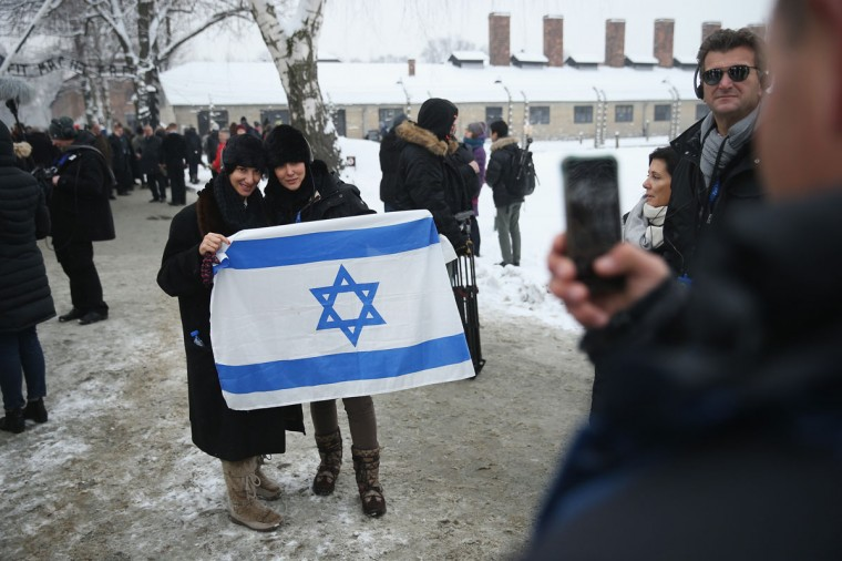 A group of visitors from Israel pose with an Israeli flag while visiting the former Auschwitz I concentration camp, which is now a museum, on January 26, 2015 in Oswiecim, Poland. (Photo by Sean Gallup/Getty Images)