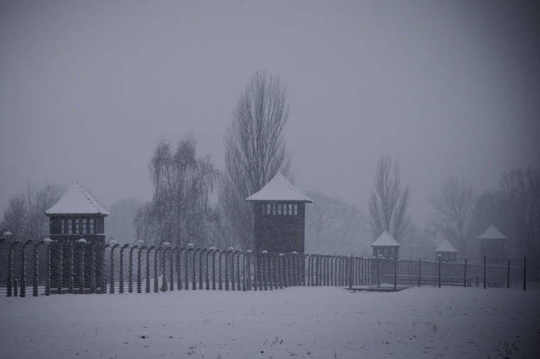 Snow falls on watchtowers and a barbed-wire fence at the memorial site of the former Nazi concentration camp Auschwitz-Birkenau in Oswiecim, Poland, on January 25, 2015. (JOEL SAGET/AFP/Getty Images)