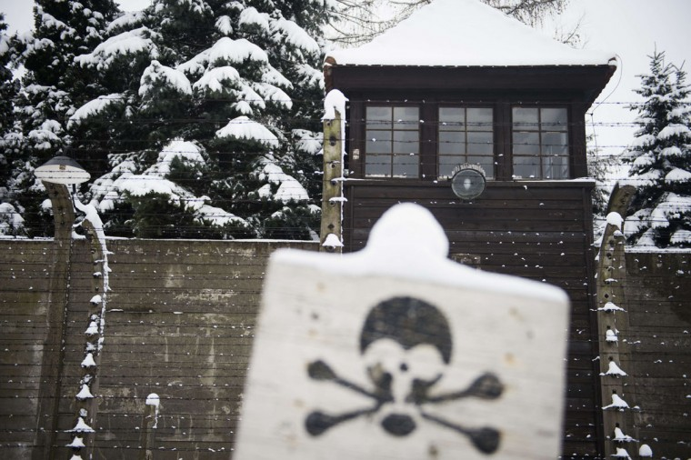 A warning sign is seen in front of a watch tower of the former Auschwitz concentration camp held by the Nazis in Oswiecim on January 26, 2015. (ODD ANDERSEN/AFP/Getty Images)