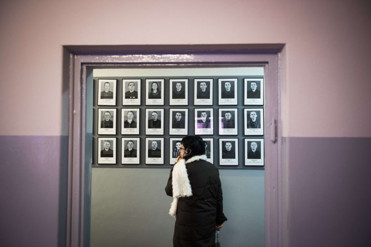 A woman looks at pictures depicting deceased inmates displayed on the wall of a barrack as she visits the former Auschwitz concentration camp in Oswiecim on January 26, 2015. (ODD ANDERSEN/AFP/Getty Images)