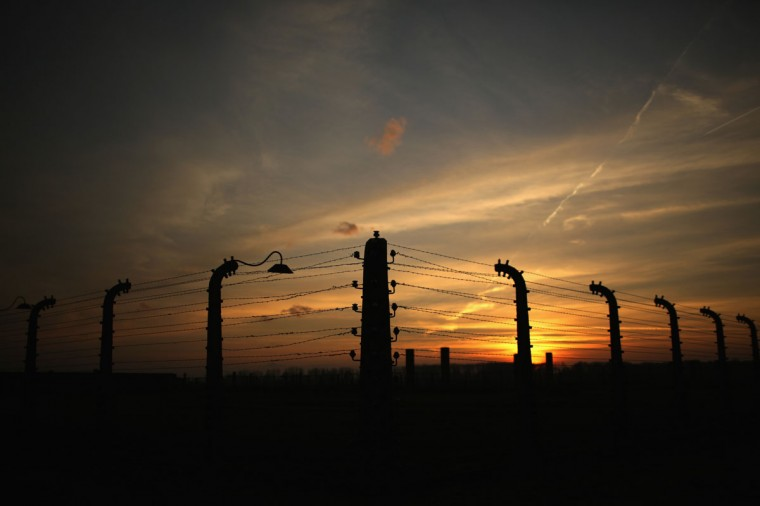 The sun rises over the electrified fence of the Auschwitz II Berkenau extermination camp on November 11, 2014 in Oswiecim, Poland. (Photo by Christopher Furlong/Getty Images)