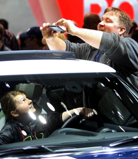 Donivan Navock photographs his daughter, Veronica Navock, in a Mini Cooper S at the North American International Auto Show at Cobo Center in downtown Detroit. Saturday was the first day the show was open to the public. It runs through Jan. 25. (Kirthmon F. Dozier/AP Photo/Detroit Free Press, )