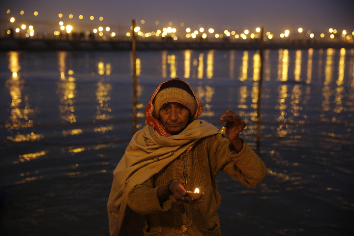 A Hindu pilgrim performs evening rituals at the Sangam, the confluence of the Rivers Ganges, Yamuna and mythical Saraswati, during the annual Magh Mela traditional fair in Allahabad, India. Hundreds of thousands of devout Hindus are expected to take holy dips at the confluence during the astronomically auspicious period of over 45 days celebrated as Magh Mela. (Rajesh Kumar Singh/AP Photo)