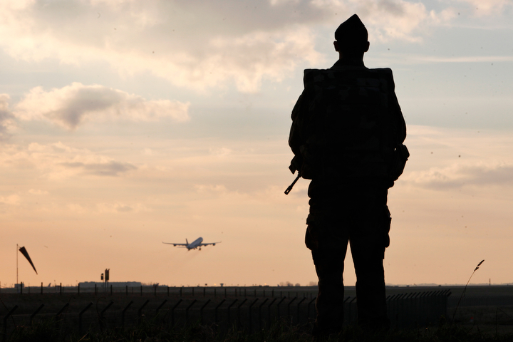 A plane takes off as a French soldier patrols at the Roissy Charles de Gaulle airport, in Roissy, north of Paris. France ordered 10,000 troops into the streets Monday to protect sensitive sites — nearly half of them to guard Jewish schools — as it hunted for accomplices to the Islamic militants who left 17 people dead as they terrorized the nation. (Thibault Camus/AP Photo)