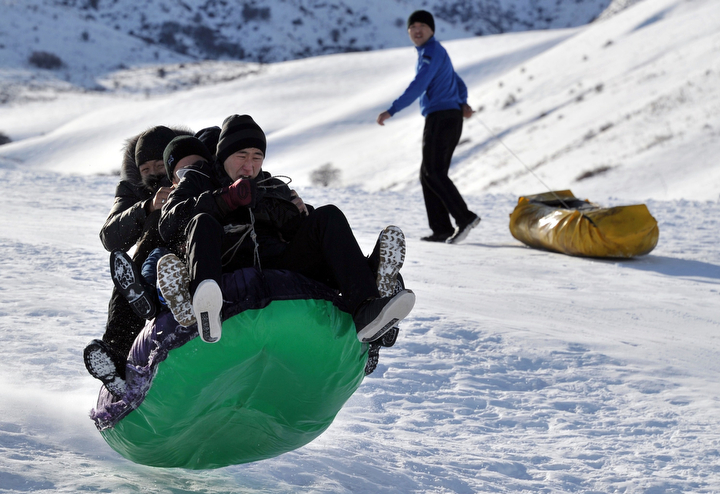 People ride on a sled in the snow near the village of Prokhladnoe, some 20 km from Bishkek as temperatures in the Chuy valley reached 10 C (50 F). (Vyacheslav Oseledko/AFP-Getty Images)