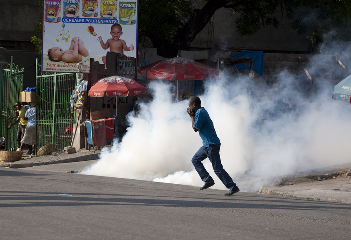 A demonstrator runs for cover as National Police fire tear gas at protesters demanding the resignation of President Michel Martelly, in Port-au-Prince, Haiti. The protest was the latest in a series of demonstrations demanding Martelly leave office before his term expires next year. (Dieu Nalio Chery/AP Photo)