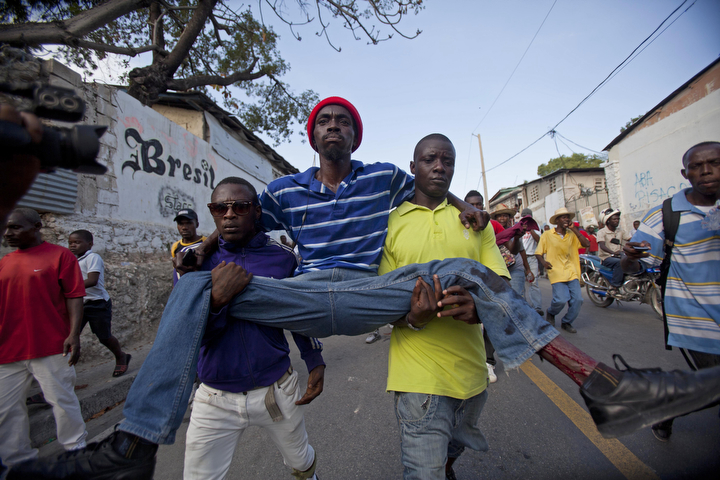 Protesters carry a man who was shot in his left leg after clashes broke out with national police during a demonstration to demand the resignation of President Michel Martelly, in Port-au-Prince, Haiti. The protest was the latest in a series of demonstrations demanding Martelly leave office before his term expires next year. (Dieu Nalio Chery/AP Photo)