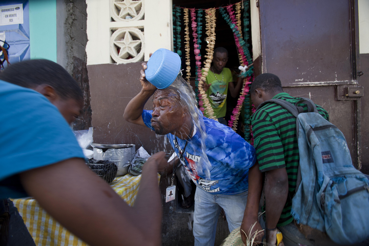 A demonstrator douses his face with water to relieve the effects of the tear gas fired by National Police during a protest to demand the resignation of President Michel Martelly, in Port-au-Prince, Haiti. The protest was the latest in a series of demonstrations demanding Martelly leave office before his term expires next year. (Dieu Nalio Chery/AP Photo)