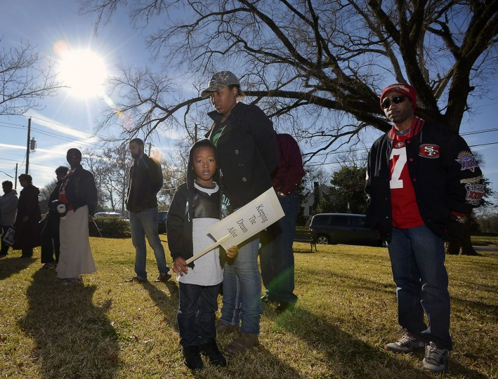Bryson Wade, front, holds a sign as he stands with Destiny Agnew during a prayer vigil before the annual Dr. Martin Luther King Jr. Day march, Monday, Jan. 19, 2015, at Eugenia Sterne Park in Nacogdoches, Texas. (AP Photo/The Daily Sentinel, Andrew D. Brosig)