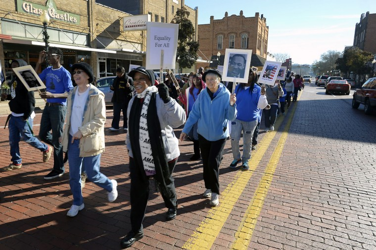 Community members sing and carry signs as they walk along Main Street during the annual Dr. Martin Luther King Jr. Day march, Monday, Jan. 19, 2015, in Nacogdoches, Texas. (AP Photo/The Daily Sentinel, Andrew D. Brosig)