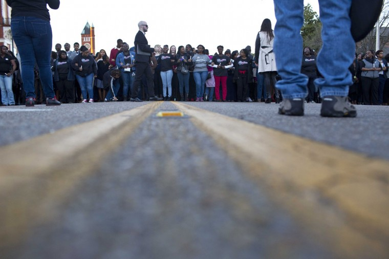 Marchers line up and lock arms before they make their way Edmund Pettus Bridge in honor of Martin Luther King Jr.,Sunday, Jan. 18, 2015, in Selma, Ala. (AP Photo/Brynn Anderson)