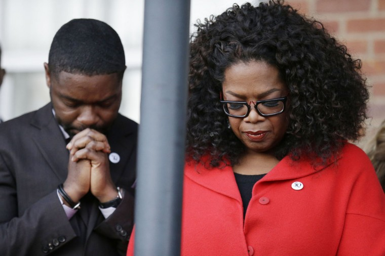 """Oprah Winfrey lowers her head to pray with David Oyelowo, who portrays Martin Luther King Jr. in the movie """"Selma"""" before they march to the Edmund Pettus Bridge in honor of Martin Luther King Jr., Sunday, Jan. 18, 2015, in Selma, Ala. (AP Photo/Brynn Anderson)"""